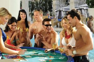 A group of people gathered around a blackjack table while in the Fortuna Pool at Caesars Palace Las Vegas
