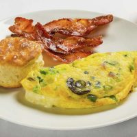 A plate with an omelet, bacon, and biscuit from the Excalibur Las Vegas buffet