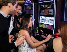 Friends playing a slot machine at Aria Las Vegas