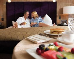 A couple in bed with a table filled with breakfast at Aria Las Vegas