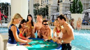 A group of pool goers playing blackjack in the Fortuna Pool at Caesars Palace Las Vegas