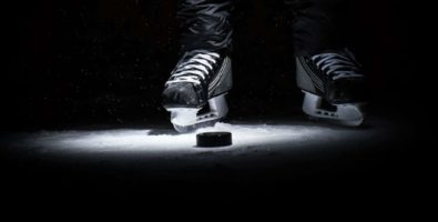 A close up on skates and a hockey puck